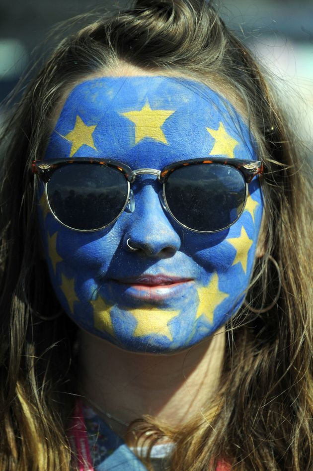 A festival-goer with a European flag painted on her face poses for a photograph on day three of