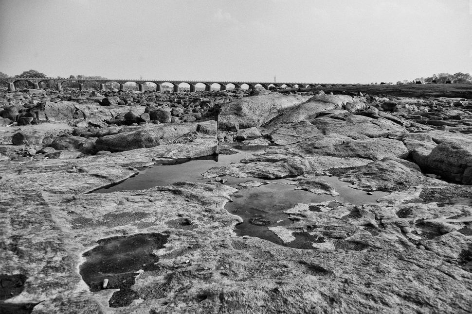 The Dhasan River once flowed along the edge of Garroli. Now all that's left is a vast rocky bed and a few pools of water refl