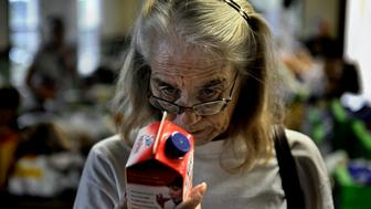 HOBE SOUND, FL - APRIL 14: Marion Mattrazzo checks the expiration date on some soy milk at a food pantry in Hobe Sound. Scores of locals waited to get a box of food but senior citizens with a number got to retrieve food first. Mattrazzo, 54, suffers from Cirrhosis of the Liver and lives on about $7,000 per year. She signed up for the SNAP program because what little income she has goes for medical related expenses (she's too young to be eligible for Medicare). She once had a vibrant construction company that suffered badly with the housing collapse in Florida. Adding to her difficulty was that her husband died two years ago. She now rents (for $200 a month) a 100 square foot shack that was tacked onto a garage. The SNAP program is a huge help to her but because she has no stove, she has to buy a lot of microwaveable foods. She's been feeling depressed of late about her current circumstances, 'I'm just existing at this point,' she said. Many low-income seniors qualify to participate in the S.N.A.P. (food stamps) program but do not receive the benefit, often because they are too proud or unaware of it. Photo by Michael S. Williamson/The Washington Post via Getty Images