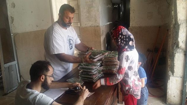 Adham handed out meals to families trapped in Aleppo during Ramadan earlier this