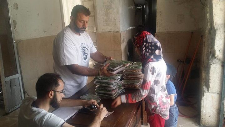 Adham handed out meals to families trapped in Aleppo during Ramadan earlier this month.