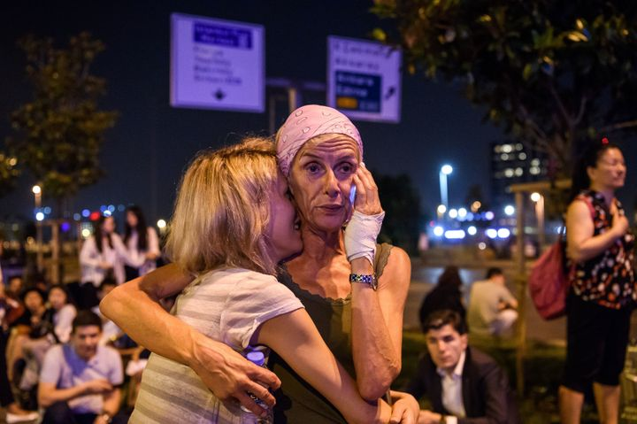 Passengers embrace outside Istanbul Ataturk Airport on June 28 after three suicide bombers attacked outside of the