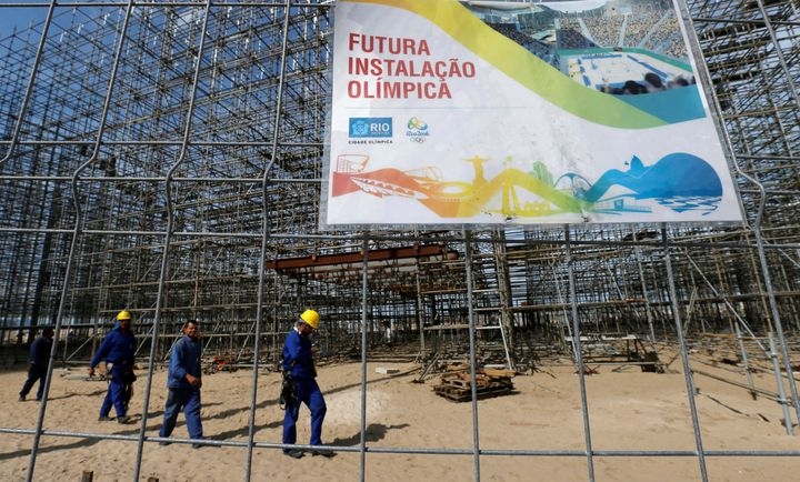 Workers are pictured at the construction site of the beach volleyball venue for 2016 Rio Olympics on Copacabana beach.