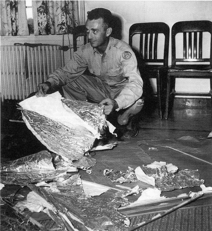In July 1947, Maj. Jesse Marcel of the Roswell Army Air Field in New Mexico shows members of the press alleged pieces of a we