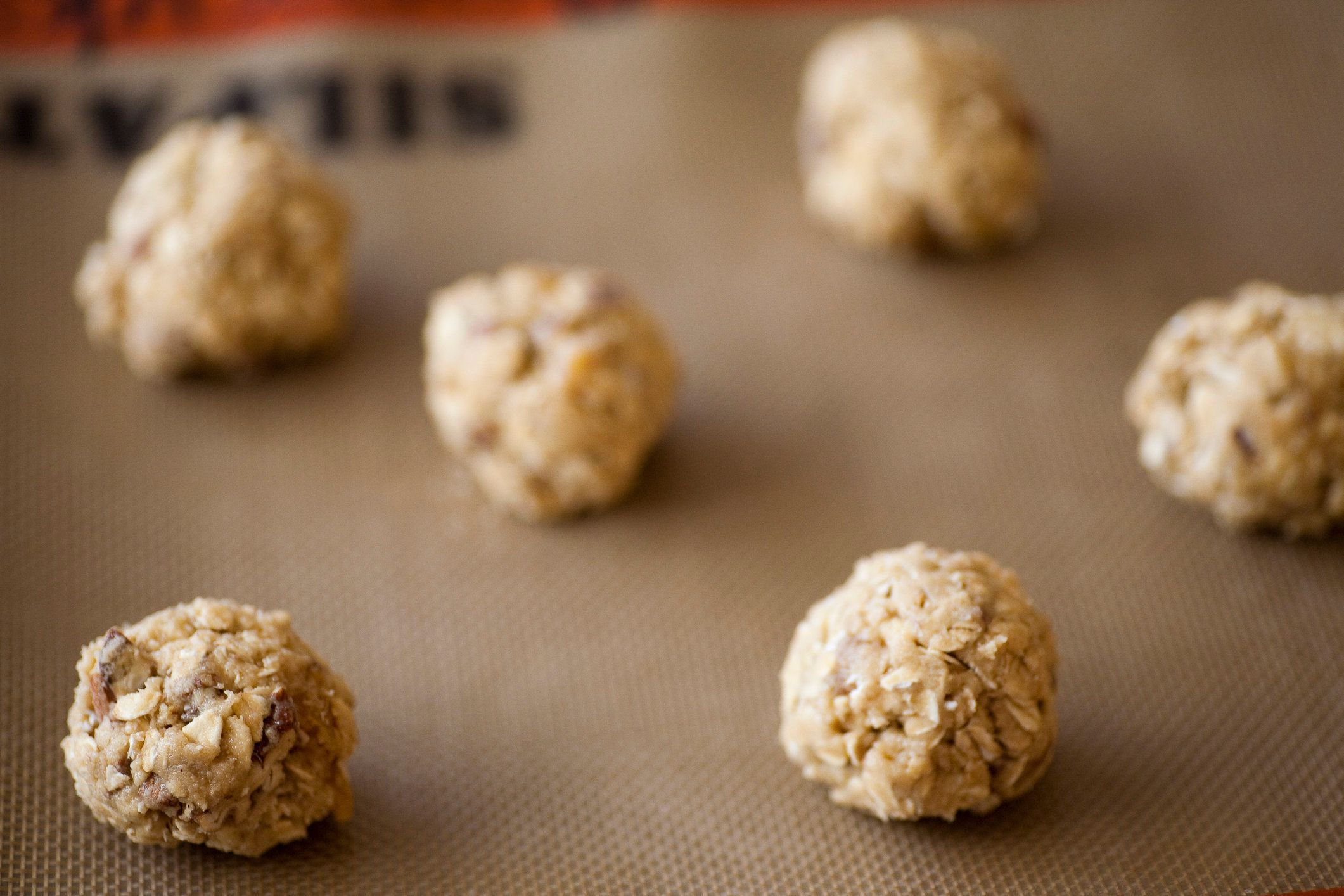 Balls of freshly made organic oatmeal cookie dough sit on a cookie sheet in a kitchen in Seattle, Washington.