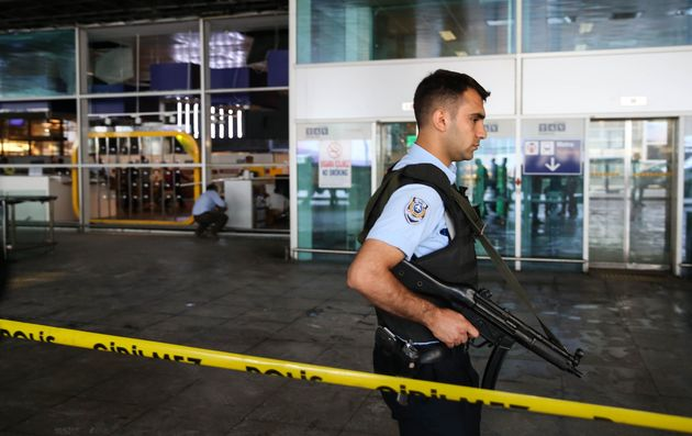 A Turkish police officer stands guard at Istanbul Ataturk Airport after air traffic returned to...
