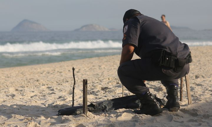 A police officer kneels over a body part, covered in a plastic bag, which was discovered on Copacabana Beach near the Olympic