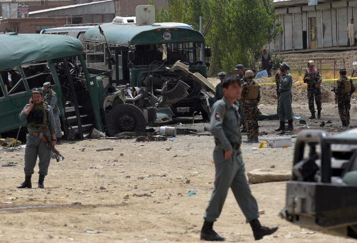 Afghan security personnel gather near the wreckage of buses which were carrying police cadets, at the site of a bomb attack o