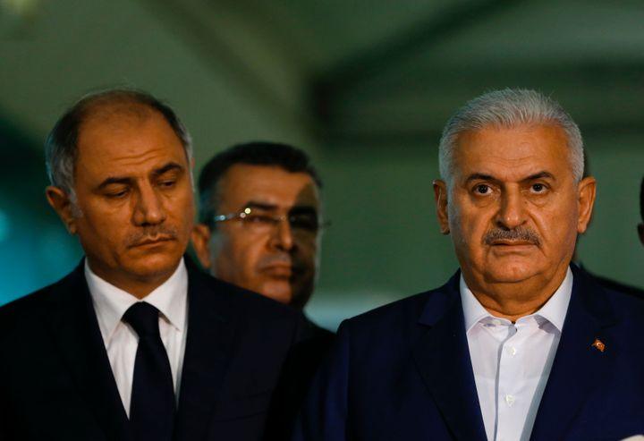 Turkey's Prime Minister Binali Yildirim (R) speaks to the press next to the Interior Miinister Efkan Ala at the Ataturk airpo