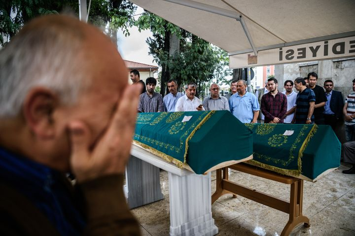 People mourn next to coffins of Maryam Amiri, Karime Amiri, Zahra Amiri and Huda Amiri on June 30, 2016 in Istanbul during th