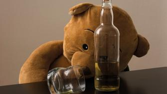 Drunk teddy bear lying on the table of his house