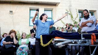 The mother of Israeli girl, Hallel Yaffa Ariel, 13, who was killed in a Palestinian stabbing attack in her home in the West Bank Jewish settlement of Kiryat Arba, mourns during her funeral at a cemetery in the West Bank city of Hebron June 30, 2016. REUTERS/Ronen Zvulun