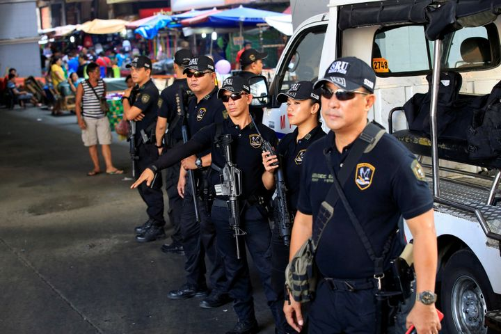 Members of the Philippine National Police Special Reaction Unit gather as part of a police visibility operation along a main