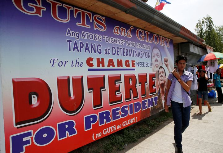 """Residents walk past an election campaign poster of leading presidential candidate Rodrigo """"Digong"""" Duterte in Davao city."""