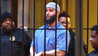 Officials escort 'Serial' podcast subject Adnan Syed from the courthouse following the completion of the first day of hearings for a retrial in Baltimore on Wednesday, Feb. 3, 2016. (Karl Merton Ferron/Baltimore Sun/TNS via Getty Images)