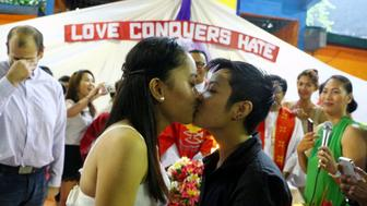 PHILIPPINES - 2016/06/26: Filipino LGBT (Lesbian, Gay, Bisexual and Transgender) couples Nadel Ambayec, 25 yrs old (left) and Maryt Grace Timkang, 20 yrs old (right) kiss each other during the mass wedding officiated by Rev. CJ Agbayani Jr. (center) of LGBT Christian Church at Mendoza Covered Court in Brgy. Pinalabanan. (Photo by Gregorio B. Dantes Jr./Pacific Press/LightRocket via Getty Images)