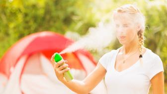 USA, Florida, Tequesta, Woman spraying head with bug spray