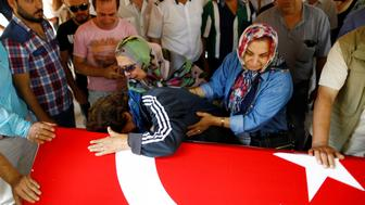 Relatives of Gulsen Bahadir, a victim of Tuesday's attack on Ataturk airport, mourn at her flag-draped coffin during her funeral ceremony in Istanbul, Turkey, June 29, 2016. REUTERS/Osman Orsal