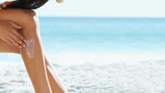 Cropped view of a young woman putting sun cream on her legs