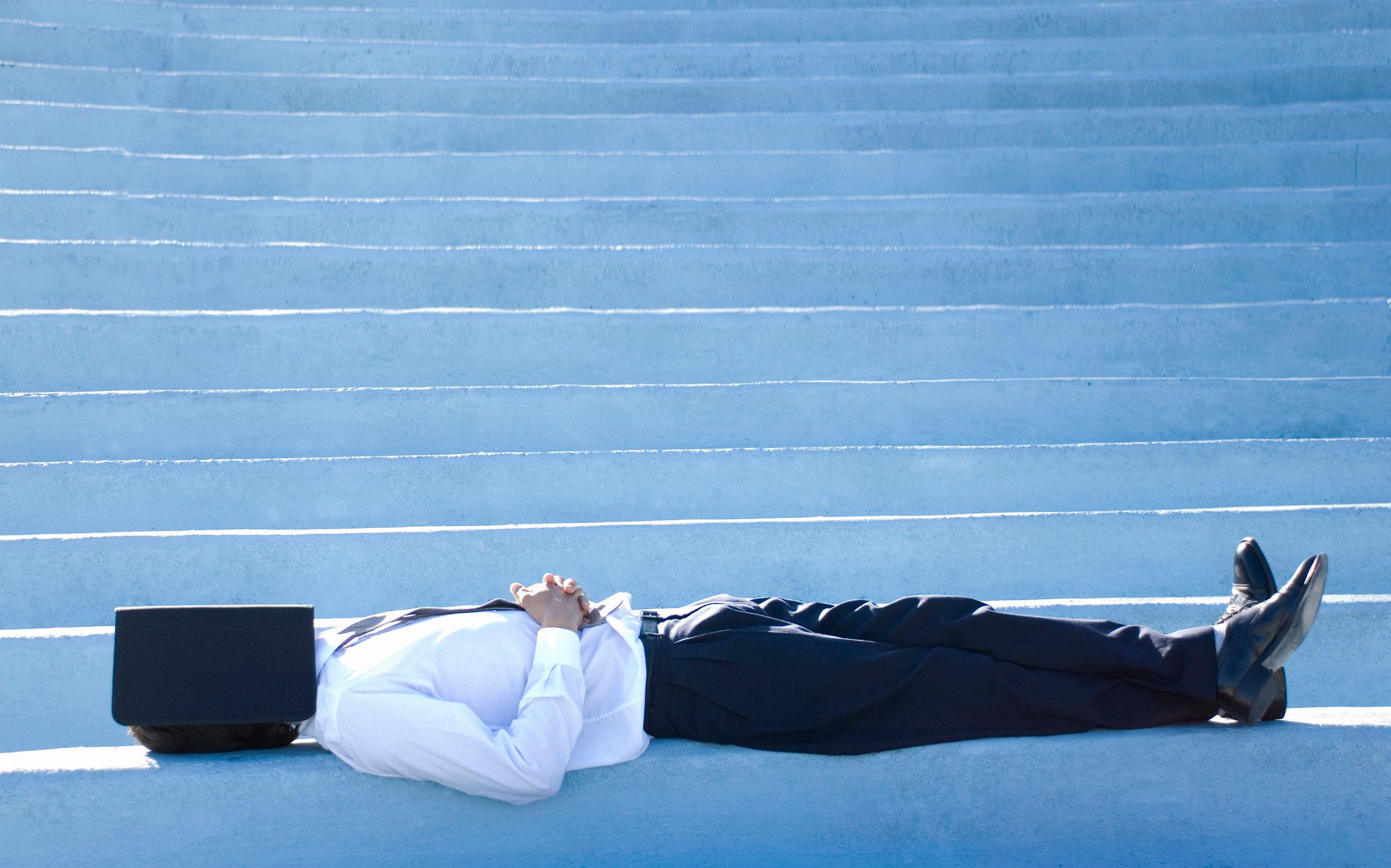 Businessman lying on steps with his face covered with a notebook, Montevideo, Uruguay
