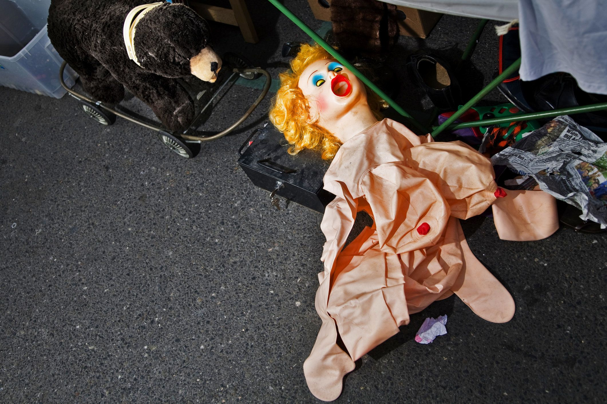 A sex doll on the floor at the viennese Naschmarkt is chasen by a doll-bear