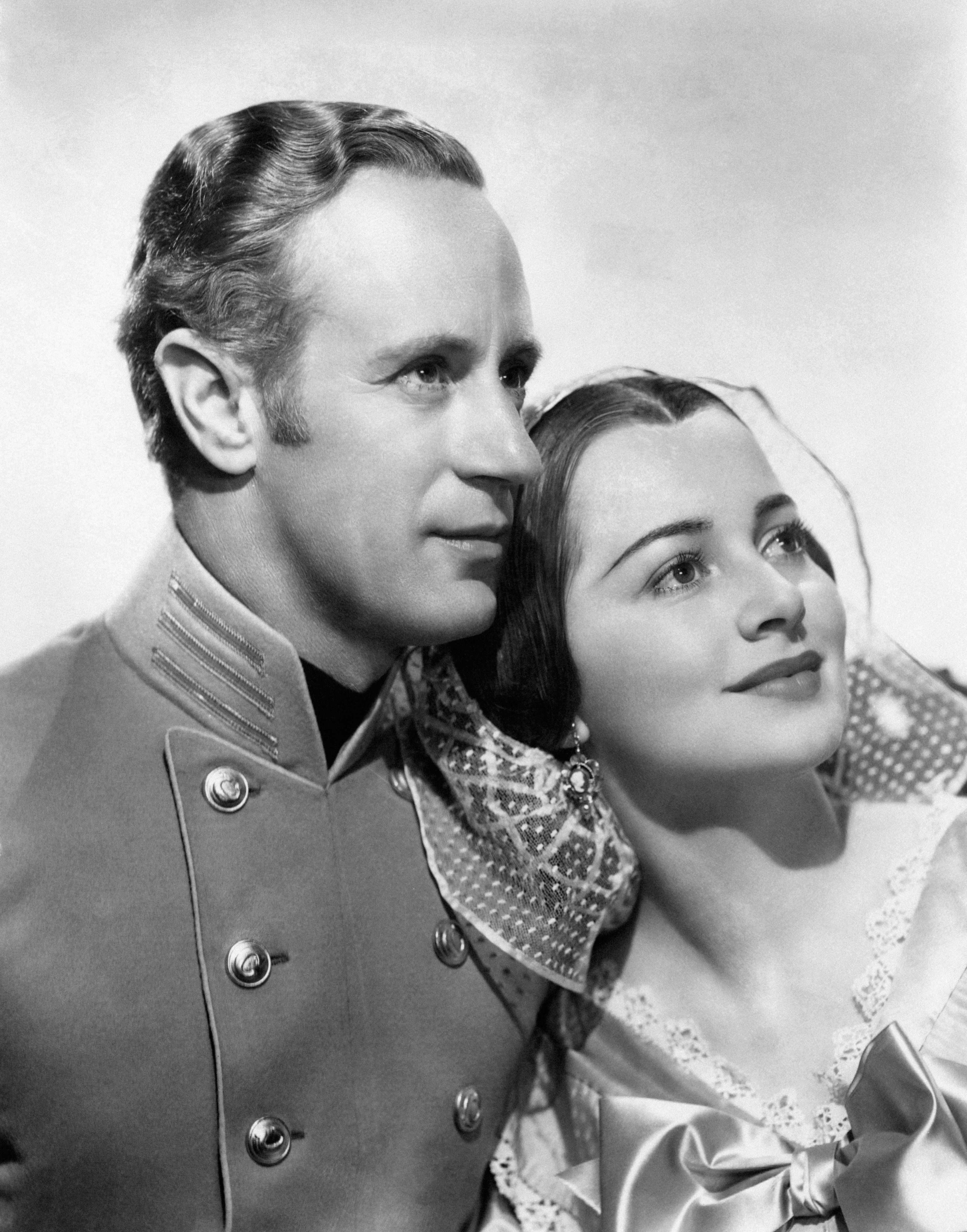 Half-length portrait of smiling actors Leslie Howard and Olivia De Havilland, who play the roles of Ashley Wilkes and Melanie Hamilton, wearing stage costumes in a scene from the movie Gone with the Wind by Victor Fleming. United States, 1939. (Photo by Mondadori Portfolio via Getty Images)