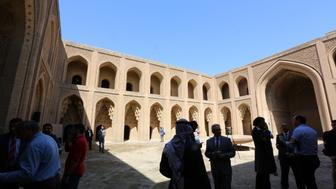 A picture taken on March 12, 2016 shows visitors at Qasr al-Abbasi Palace in the al-Maiden neighbourhood of Baghdad during a ceremony marking one year after the destruction done by the Islamic State group (IS) at the archaeological site of Nimrud that lies on the Tigris River around 30 kilometres (18 miles) southeast of Mosul. Nimrud, on UNESCO's tentative world heritage list, was founded in the 13th century BC and was considered the jewel of the Assyrian era. According to the Iraqi government, IS militants bulldozed the site on March 5.  / AFP / SABAH ARAR        (Photo credit should read SABAH ARAR/AFP/Getty Images)