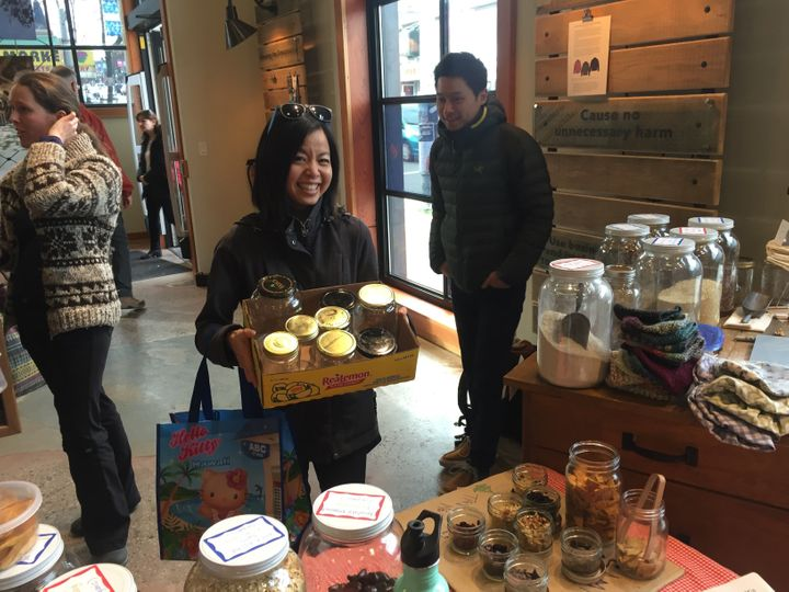 A shopper shows off her collection of glass jars at Zero Waste Market in Vancouver.