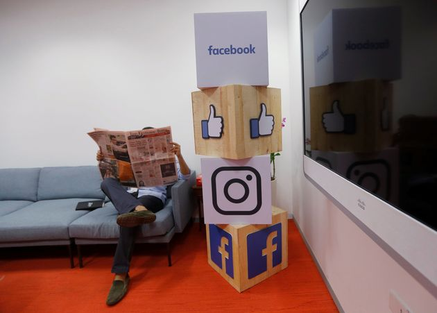 A man reads articles in a newspaper -- not on Facebook -- at the company's office in Mumbai,