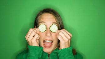 Portrait of young adult Caucasian woman on green background holding cucumber slices over her eyes.