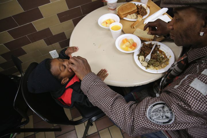 A father feeds his son dinner at a soup kitchen run by the Food Bank For New York City. The food bank distributes dry, canned