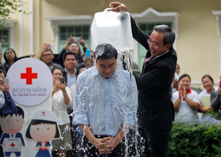 """A man dumps a bucket of ice water as part ofthe """"Ice Bucket Challenge"""" at the Thai Red Cross Society. The challenge, ai"""