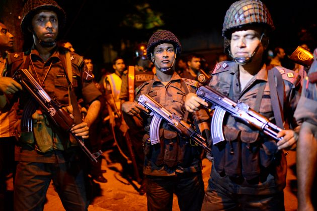 Bangladeshi security stand guard near a restaurant under attack by gunmen in the early hours of July...