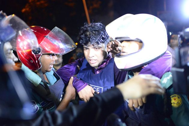 An injured Bangladeshi policeman being assisted after a granade attack at a restaurant nearby in the...