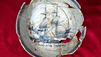 """A punch bowl reading """"Success to the Tryphena"""" features a ship that was used by the colonists in the 1700s."""