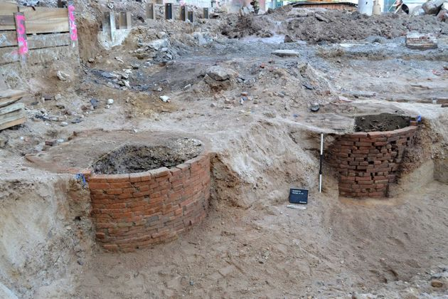 Two of the 12 brick-lined privies that were uncovered are seen. These vaults were used as outhouses and...