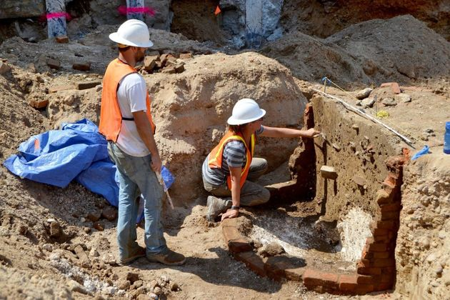 Archaeologists are seen excavating one of the privies uncovered at the site that will be transformed...