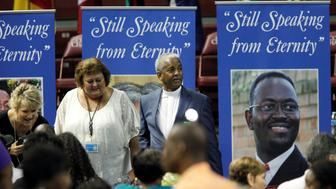 The Rev. Anthony Thompson, husband of victim Myra Thompson stands around photos of victims before a memorial ceremony marking the first anniversary of the shootings at Emanuel AME Church during a prayer service where nine people were killed by a gunman, in Charleston , South Carolina U.S. June 17, 2016. REUTERS/Randall Hill