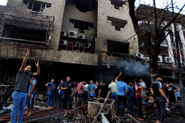 People gather at the site of a suicide car bomb in the Karrada shopping area, in Baghdad, Iraq July 3,