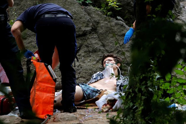 Medics stand over a man who was injured after an explosion in Central Park, in Manhattan, New