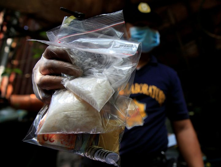 A member of the Philippine National Police (PNP) investigation unit shows confiscated methamphetamine, known locally as Shabu