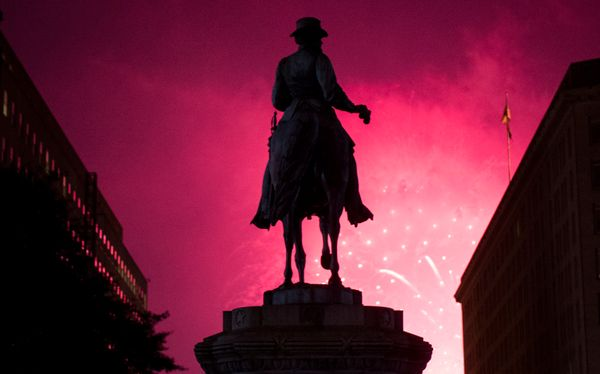 The statue of Gen. James McPherson, in McPherson Square near the White House, is silhouetted by the Independence Day firework