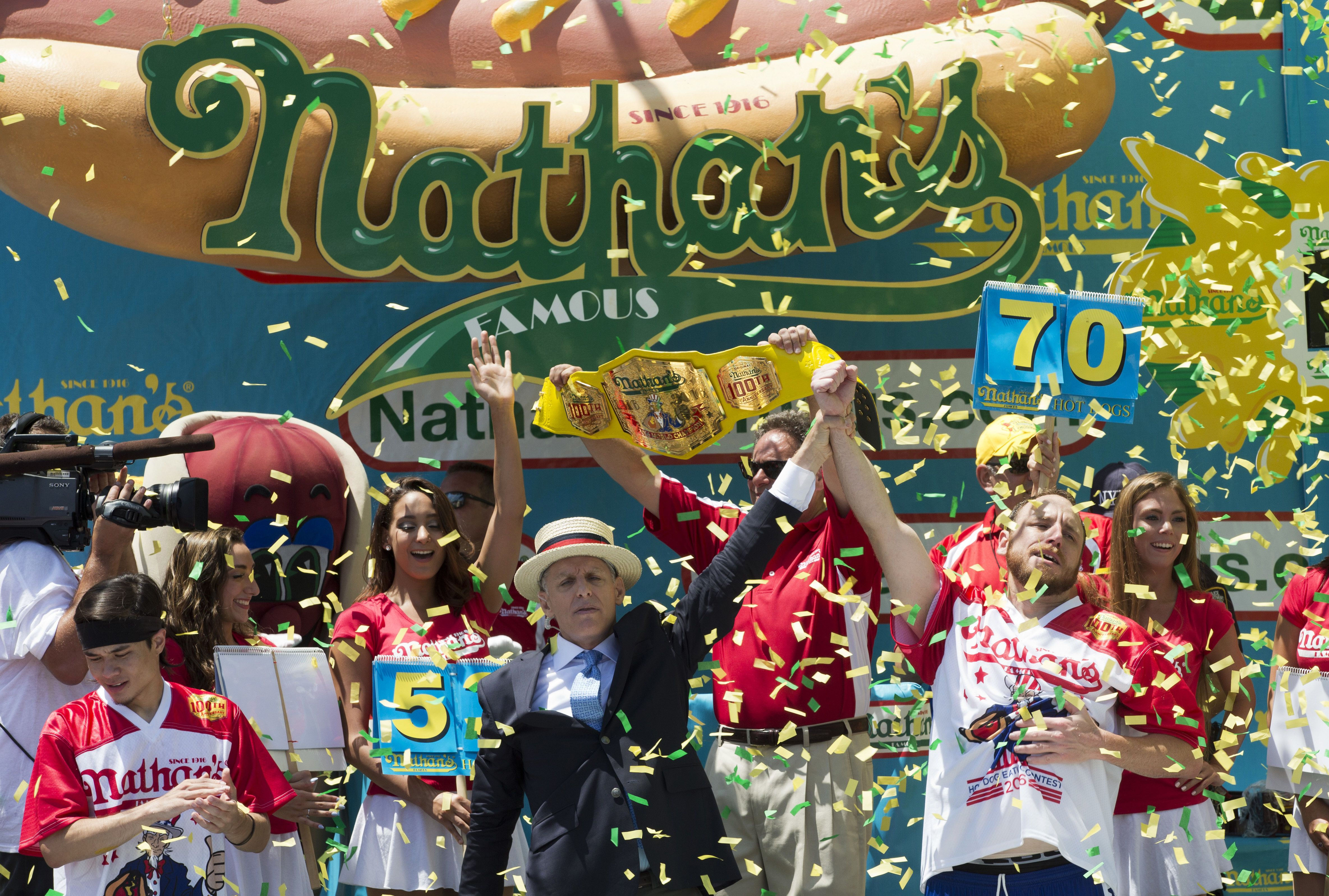 Joey Chestnut, right, is declared Nathan's Famous Fourth of July International Hot Dog Eating Contest men's competition winner, Monday, July 4, 2016, in New York. Chestnut came in first eating 70 hot dogs and buns in 10 minutes. Matt Stonie came in second eating 53 hot dogs and buns in 10 minutes. (AP Photo/Mary Altaffer)