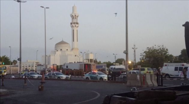 General view of security personnel in front of a mosque as police stage a second controlled explosion...
