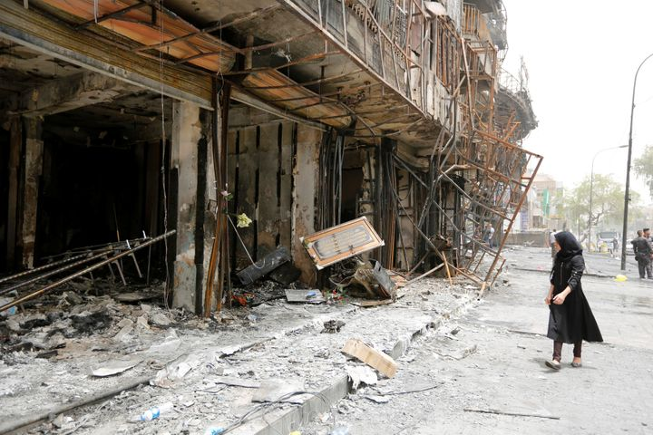A girl walks past the site after a suicide car bomb attack at the shopping area of Karrada, a largely Shi'ite district, in Ba