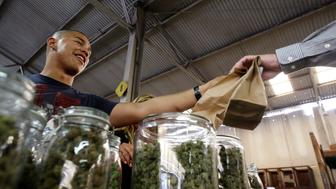 Grower Anthony Nguyen sells marijuana at the medical marijuana farmers market at the California Heritage Market in Los Angeles, California July 11, 2014. The first-ever cannabis farmers market in Los Angeles began on July 4 and opens weekly from Friday to Sunday.    REUTERS/David McNew  (UNITED STATES - Tags: DRUGS SOCIETY BUSINESS)