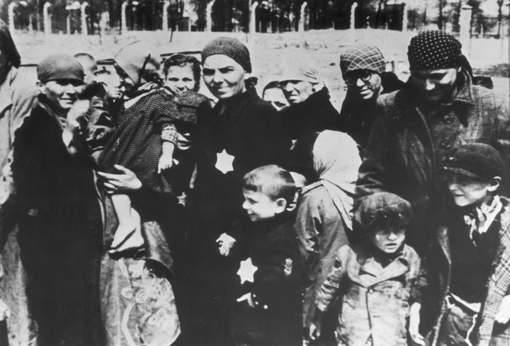 Jewish women and children, some wearing the yellow Star of David patch on their chests, at the Auschwitz concentration camp.