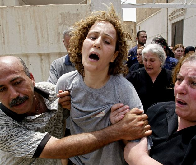 The mother of Rami Saad, 4, and Sami Saad, 6, cries out during the funeral of her two children who died...