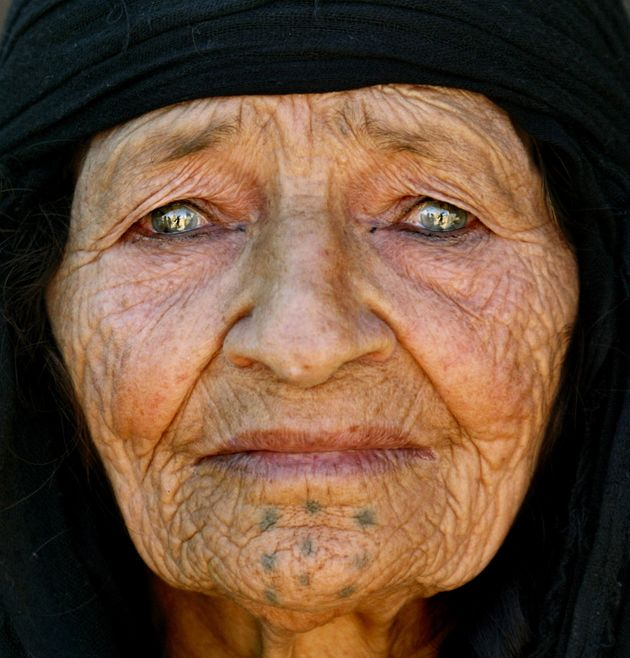 An elderly Kurdish woman looks out from her tent at Ruweished, near Jordan's eastern border with Iraq...