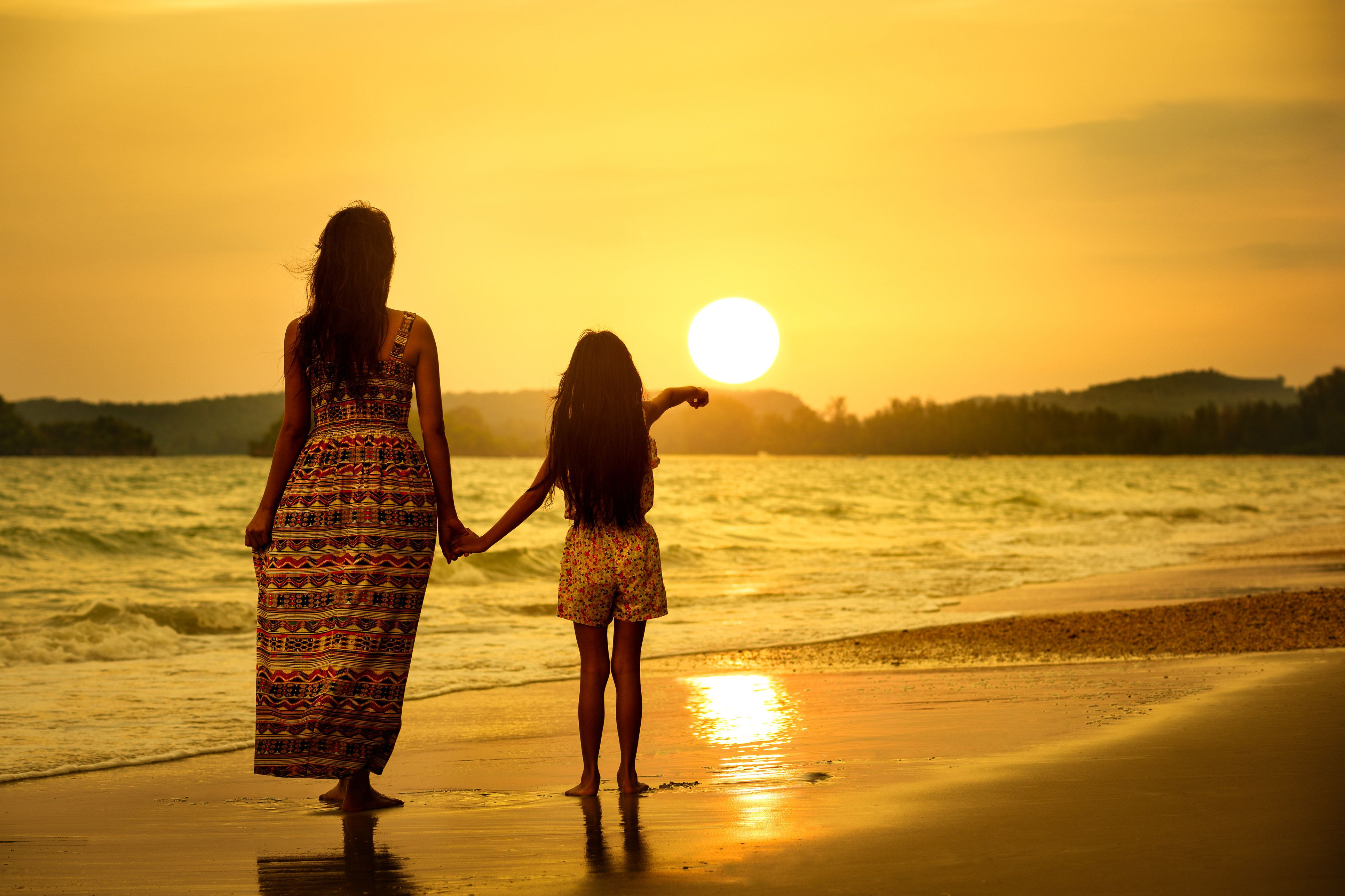 Rear view of a mother and daughter standing on the beach.
